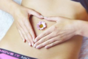 health and wellness business name featured image- fit women with flower heart on stomach